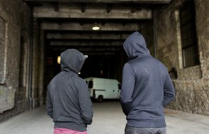 Two criminals in hoodies in front of a van in a tunnel, meant to represent cooking oil theft.